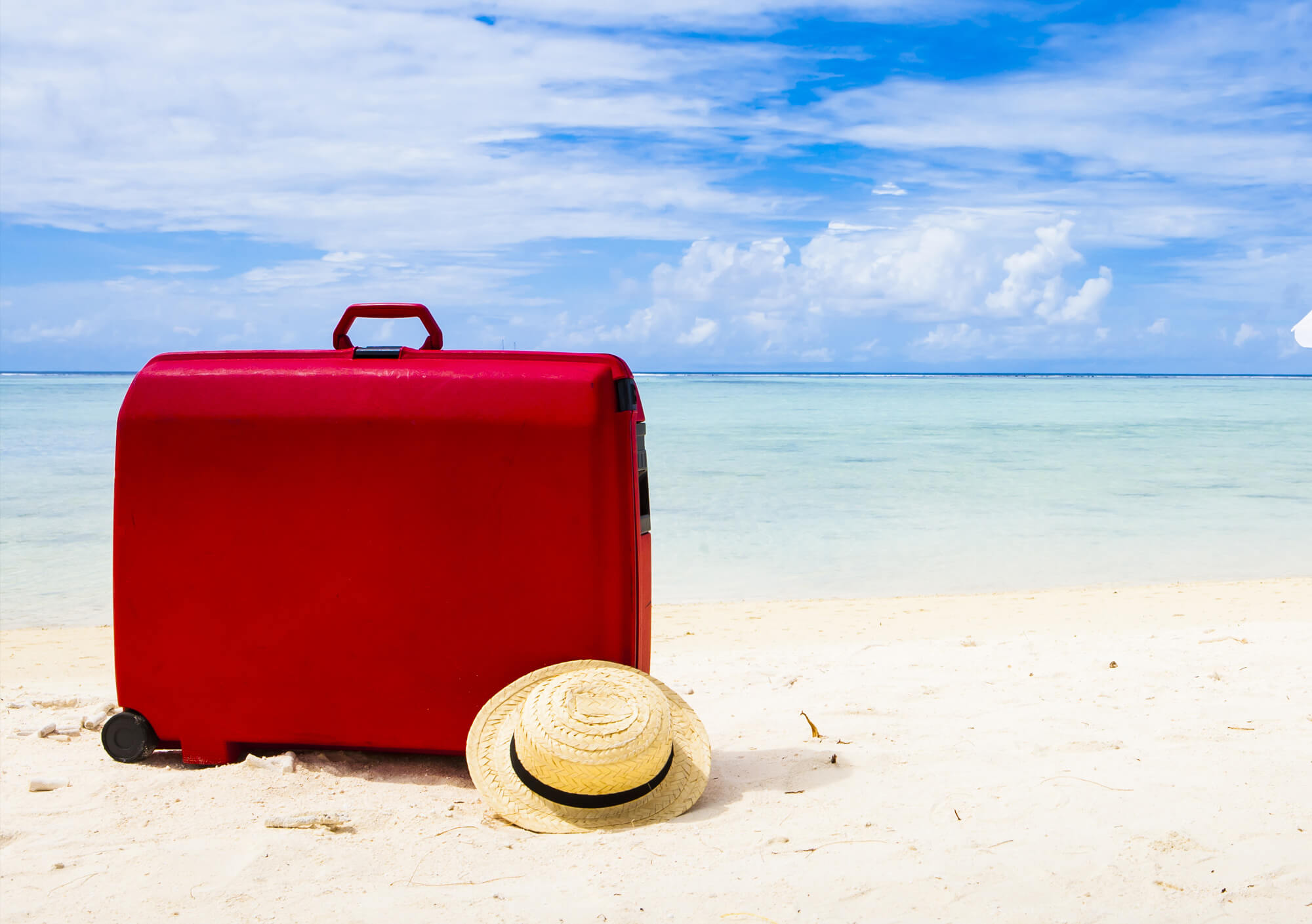 Red suitcase on beach
