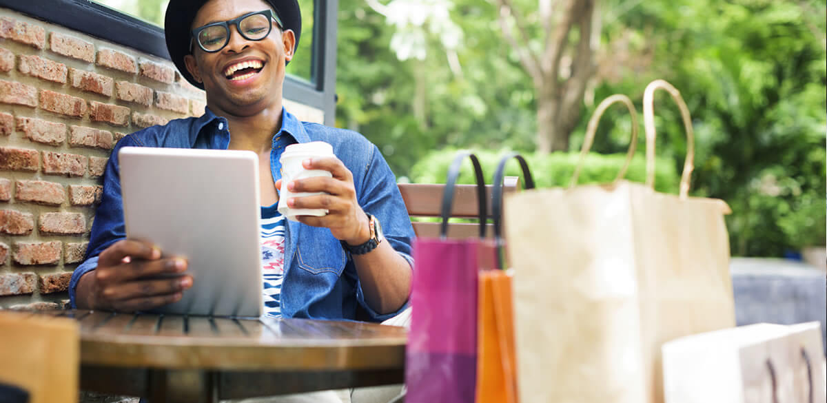Happy shopper drinking coffee and browsing tablet